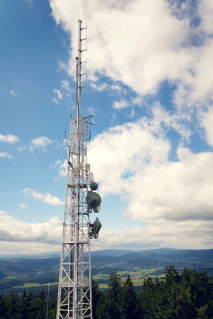 Aerials and transmitters on telecommunication tower with mountains in background Stock Photo