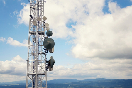 Aerials and transmitters on telecommunication tower with mountains in background 写真素材