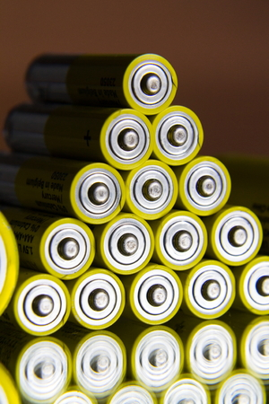 Stack of yellow AA batteries close up, electricity storage concept