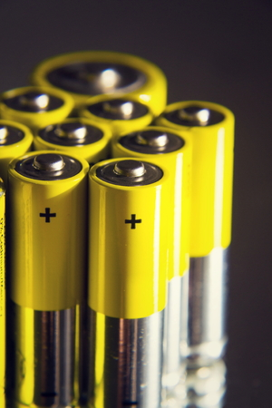 Yellow double A batteries reflecting in mirror, electricity storage concept