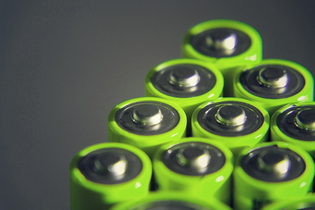 Stack of green AA batteries close up, electricity storage concept