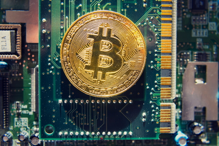 Golden bitcoin coin lying on computer motherboard, cryptocurrency mining concept