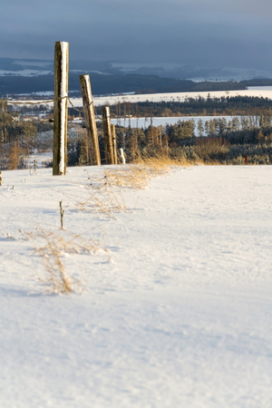 Fence poles in snowy winter country sunny day, weather forecast concept Stock Photo