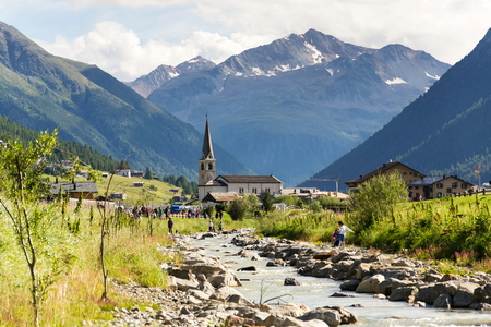 LIVIGNO, ITALY - AUGUST 1: People around Spol River with church of Santa Maria in background on 1 August 2016 in Livigno, Italy.