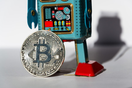 Vintage tin toy robot with bitcoin coin, cryptocurrency mining concept Stock Photo