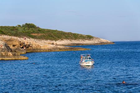 PREMANTURA, CROATIA - JULY 26: Boat with swimming people on Kamenjak peninsula by the Adriatic Sea on July 26, 2016 in Premantura, Croatia.