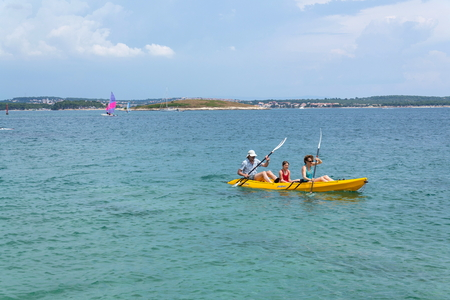 PREMANTURA, CROATIA - JULY 28: Tourists sailing on kayak on Kamenjak peninsula by the Adriatic Sea on July 28, 2016 in Premantura, Croatia.