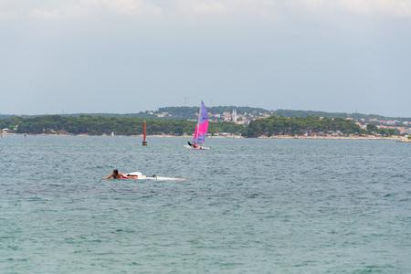 PREMANTURA, CROATIA - JULY 28 2016: Tourists windsurfing and paddleboarding around Kamenjak peninsula by the Adriatic Sea on July 28, 2016 in Premantura, Croatia.