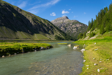 Spol River flowing in Lake Livigno, Corno Brusadella Mountain background
