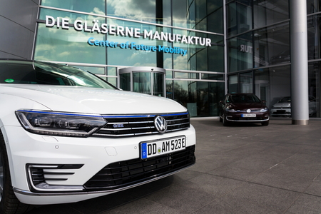 DRESDEN, GERMANY - APRIL 2 2018: Plug-in hybrid Volkswagen Golf GTE and e-Golf electric cars stand by charging station in front of the Glaserne Manufaktur - Transparent Factory on April 2, 2018 in Dre
