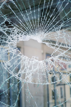 Hole in broken shattered security glass, insurance security crime concept