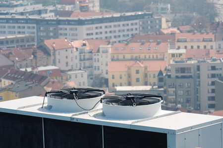 Air conditioning ventilators on roof with houses in background Stock Photo