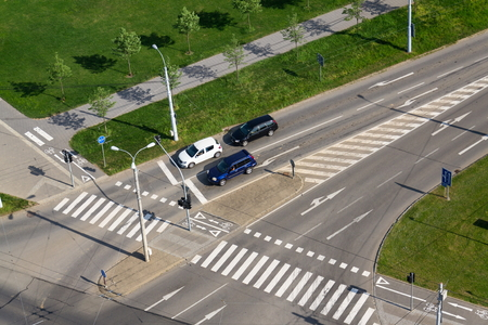 Cars standing in front of crosswalk on crossroad, aerial view