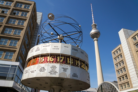 BERLIN, GERMANY - APRIL 15 2018: Urania World Clock from 1969 on public square of Alexanderplatz with Fernsehturm televison tower on April 15, 2018 in Berlin, Germany.