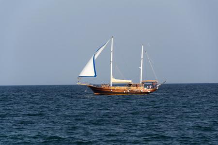 MONOPOLI, ITALY - JULY 5 2018: Ship Yasemin Sultan from mahagony tree sailing near beach Porta Vecchia on July 5, 2018 in Monopoli, Italy. Editorial