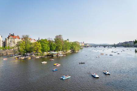 PRAGUE, CZECH REPUBLIC - APRIL 21 2018: Tourist sailing on pedal boats on Vltava river near Charles bridge on April 21, 2018 in Prague, Czech Republic.