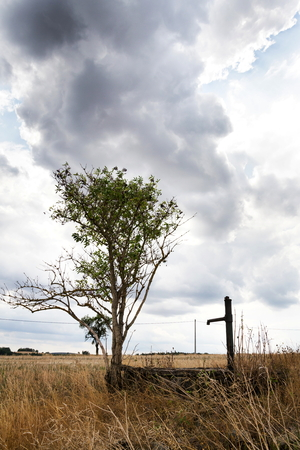 Old pump with dry soil, dramatic cloudy sky, water shortage Stock Photo