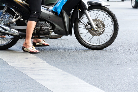 Woman on motorbike with sandals on feet stands on busy street of Ho Chi Minh City, Vietnam Stok Fotoğraf