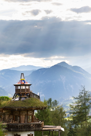 Beautiful sunset with dramatic clouds over Dachstein mountains, wooden lookout with green sod roof in foreground, Northern Limestone Alps, Schladming, romantic love peaceful meditation concept Stok Fotoğraf