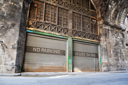 No parking place, in use 24 hours notice on old rusty vintage paint corrugated iron garage, Edinburgh, Scotland, United Kingdom, autonomous self-driving parking concept Stock Photo