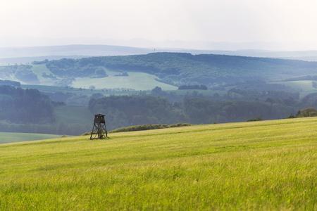 Deer stand, wooden hunters high seat hide on field, summer day, cloudy dramatic sky, Bojkovice, Uherske Hradiste district, Zlin region, White Carpathians, Czech Republic
