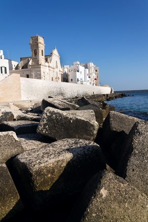 Seafront with catholic Church Chiesa San Salvatore in Monopoli, Adriatic sea, Italy, sunny summer day Stock fotó