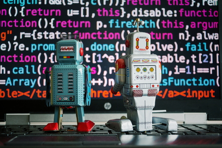 Two robots looking at laptop screen with source code, artificial intelligence, big data and deep learning concept Stock Photo