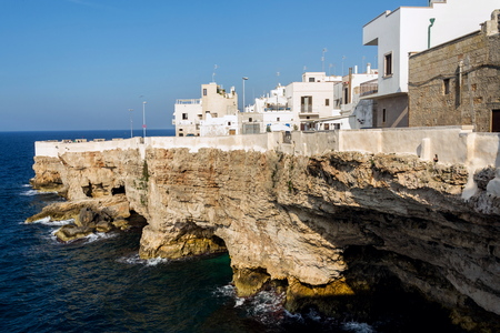 Traditional houses on dramatic cliffs with caves rising from Adriatic sea in Polignano a Mare, Italy, sunny summer day