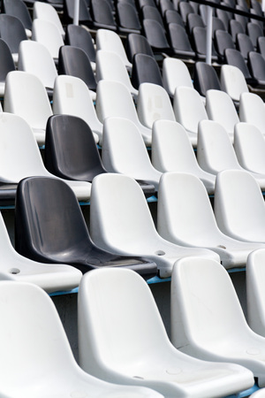 Empty black and white stadium seats mixed in rows, diversity concept