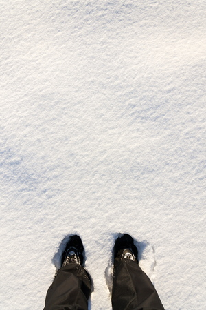 Top flat lay view of feet in waterproof winter boots in fresh snow, black trousers, white copy space background, new year resolution sport concept