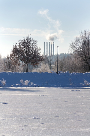 Beautiful snowy romantic winter landscape with smoking chimneys at heating plant among trees, frozen pond in foreground, sunny winter day, energy production, air pollution, climate change and global warming or freezing weather forecast concept, copy space on clear sky Stock Photo