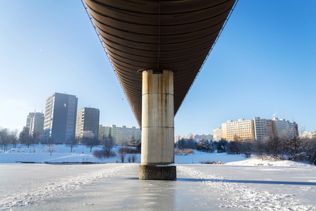 Subway overground tunnel passing over frozen pond, sunny winter freezing day, Prague between metro stations Hurka and Luziny, Czech Republic Stock Photo