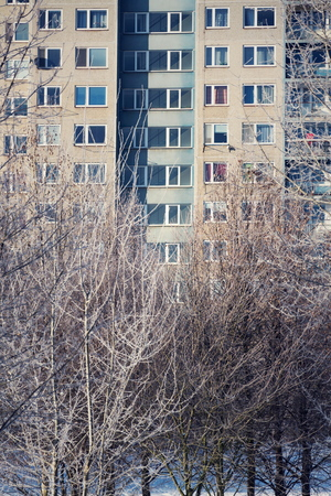 Insulated panel house apartments behind trees, high-rise block of flats, prefabricated tower blocks from concrete slabs, large panel system building, energy effeciendy building concept, cold weather sunny freezing winter day