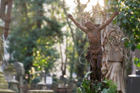 Beautiful rusty Jesus Christ crucifixion statue during sunset with common ivy, hedera helix, Olsany cemetery, Prague, Czech Republic, shallow depth of field, copy space, sunny day Stock Photo