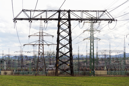 Electricity pylons conducting current from distribution power station with dramatic cloudy sky copy space background Stock Photo