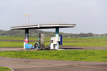 Aviation fuel filling station on airport with airfield runway in background on a sunny spring day Stock Photo