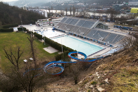 Biggest swimming complex with indoor and outdoor pools, toboggan water slide and diving towers with Vltava river in background, Podoli, Prague, Czech Republic
