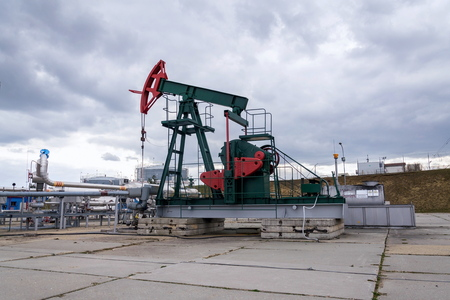 Green and red pumpjack, oil horse, oil derrick pumping oil well with dramatic cloudy sky background