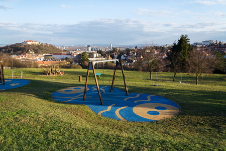 Beautiful playground with wooden swing and climbing frames for children with Spilberk castle in background, Brno, Moravia, Czech Republic, sunny day