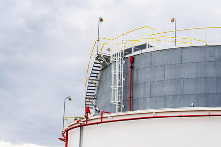 Liquid and fluid gas or oil storage tank, holder, container, dramatic sky background copy space Stock Photo