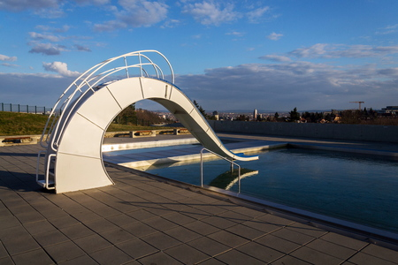 White water slide with outdoors pool, beautiful sunset, clear blue sky background Stock Photo