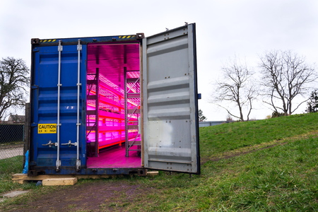 Ready to go shipping container with installed aquaponics, system combines fish aquaculture with hydroponics, cultivating plants in water under artificial lighting Stock Photo