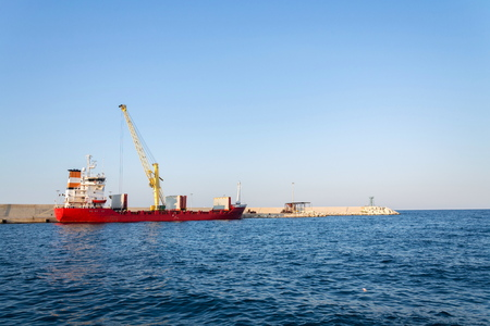 Yellow crane unloading sand from large freighter cargo ship in harbor, freight digitalization, transportation efficiency, sand shortage concept, sunny day copy space