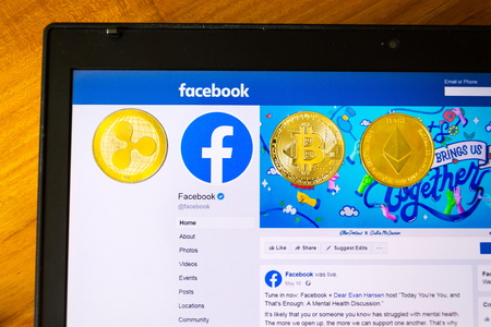 PRAGUE, CZECH REPUBLIC - JUNE 18 2019: Golden ripple, bitcoin and ethereum coins lying on homepage of Facebook launching digital wallet Calibra and cryptocurrency Libra on June 18, 2019 in Prague, Czech Republic.