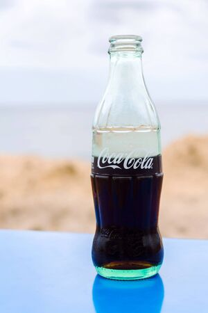 EL MEDANO, SPAIN - JULY 10 2019: Coca-Cola company logo on glass bottle with Coke with sea in background on July 10, 2019 in El Medano, Spain. Redakční