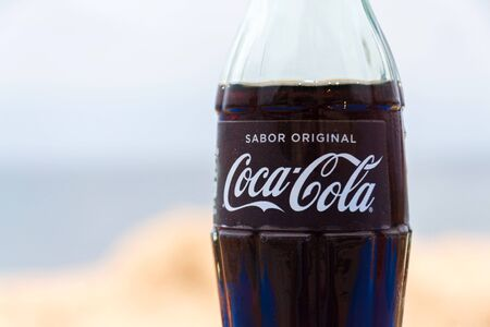 EL MEDANO, SPAIN - JULY 10 2019: Coca-Cola company logo on glass bottle with Coke with sea in background on July 10, 2019 in El Medano, Spain. Editorial