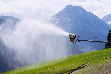 Snow making machines used to water grass on slope, sunny summer day, Wagrain ski resort, Austria Standard-Bild