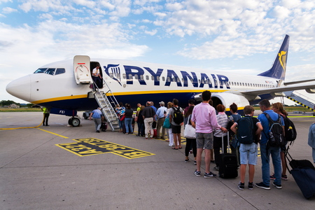 MEMMINGEN, GERMANY - JULY 6 2019: People boarding Ryanair Irish low-cost airline plane Boeing 737 with cloudy sky background on July 6, 2019 in Memmingen, Germany.