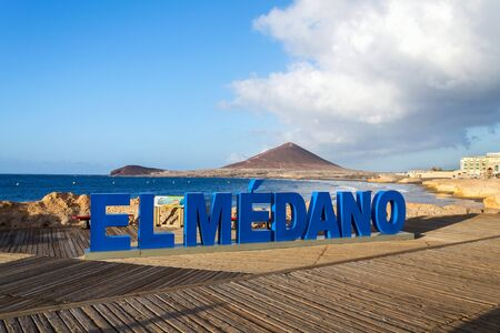 Three-dimensional sign El Medano on long promenade along the coast and beach  with Montana Roja in the background, El Medano, Tenerife, Canary Islands, Spain, sunrise on sunny summer day