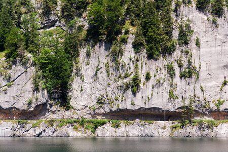 Unrecognizable people climbing on Laserer alpin via ferrata over Vorderer Gosausee lake near Gosau, Austria, sunny summer day